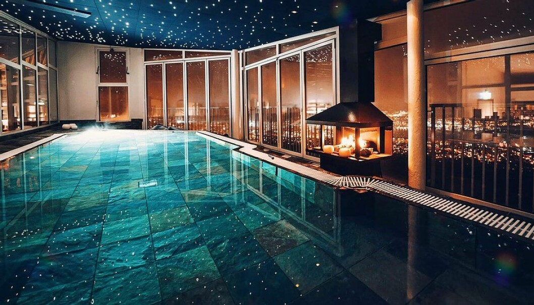 en pool inomhus med en brasa som brinner vid sidan