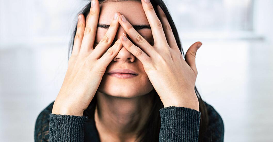 Stressad kvinna med mörkt hår gömmer ansiktet i händerna