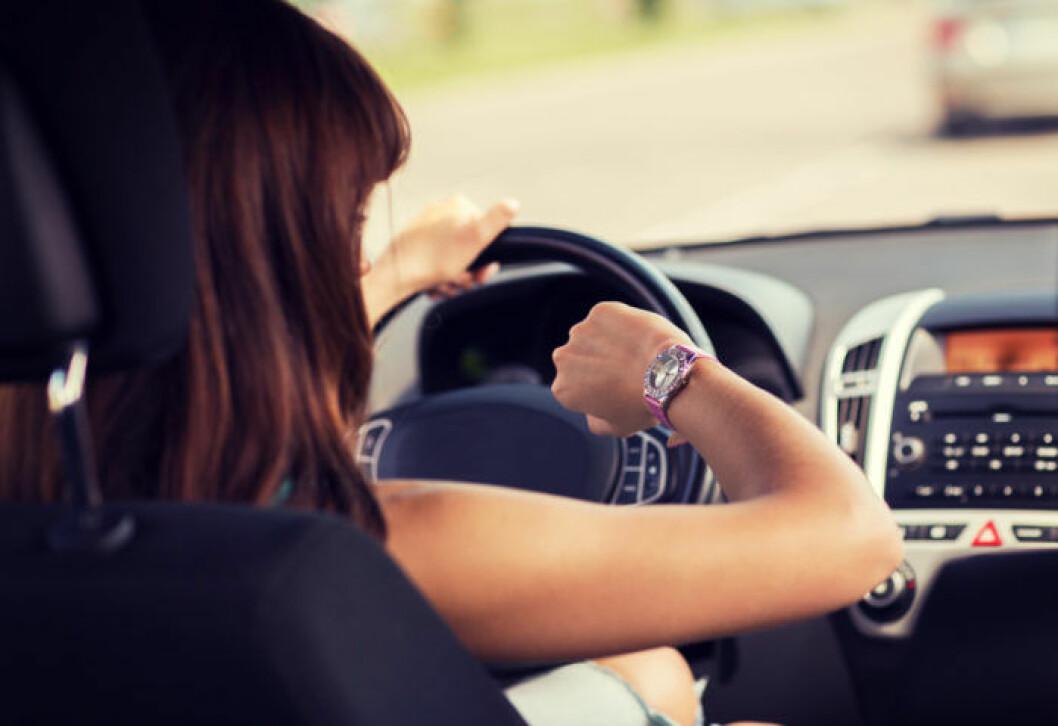 Stressad kvinna kör bil och tittar på sitt armbandsur.