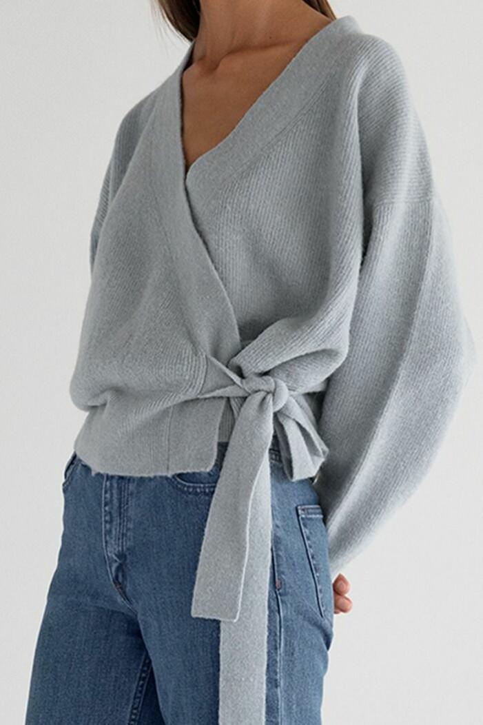 Ljusblå omlottröja i oversizad, kort modell. Stylad till blå jeans på modell. Tröja från Stylein.