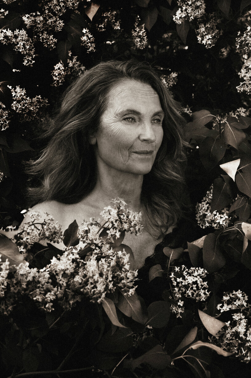 Suzanne Reuter svartvit bland blommor, avklädd