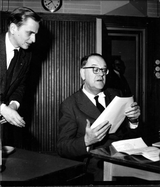En man sitter vid ett skrivbord och tittar i papper, en annan man kikar fram över hans axel. Svart vit bild