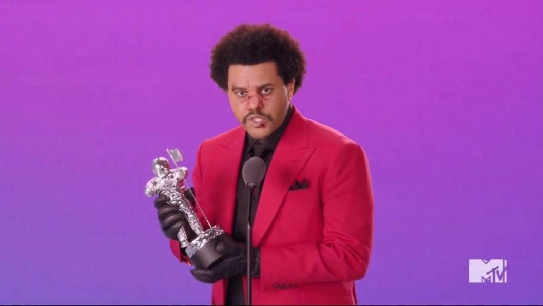 The Weeknd håller i ett pris och har röd kavaj på sig