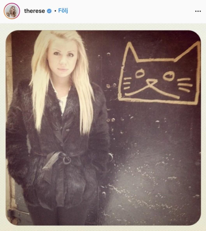 Therese Lindgren står framför en svart vägg med en målad katt på
