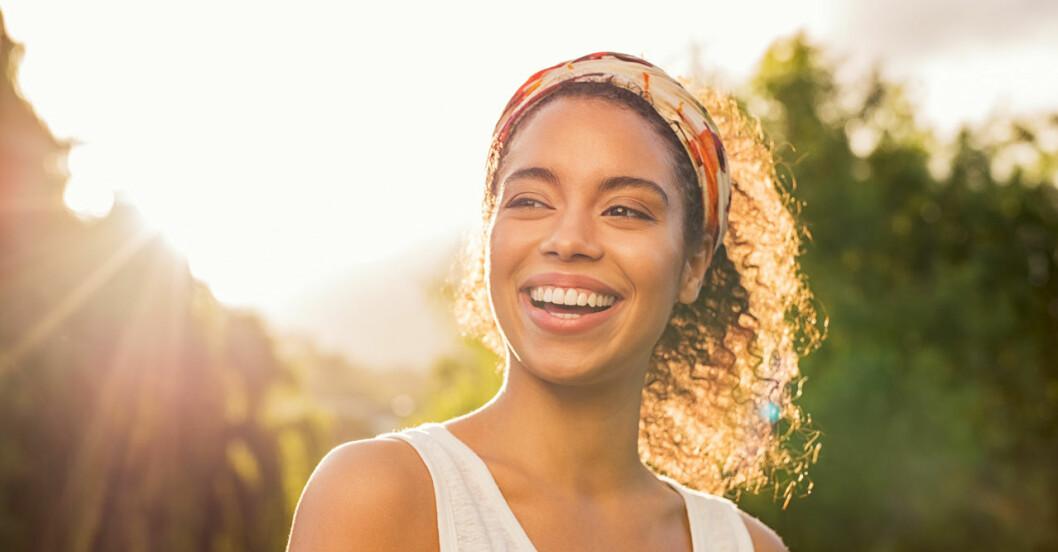 Lycklig kvinna i motljus utomhus
