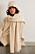 Modell med lång beige stickad halsduk och matchande mössa från Toteme.
