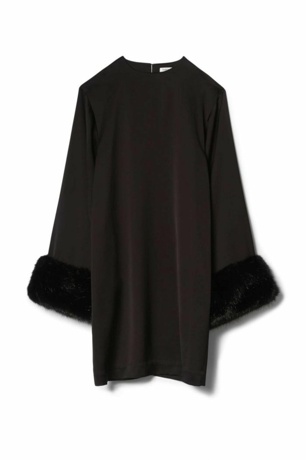 A-linjeformad svart klänning med fuskpäls vid ärmsluten. Från Totême