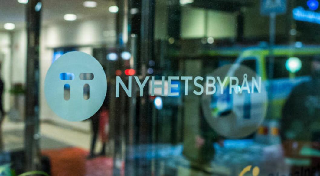 TT, Tidningarnas Telegrambyrås, logga på en dörr av glas.