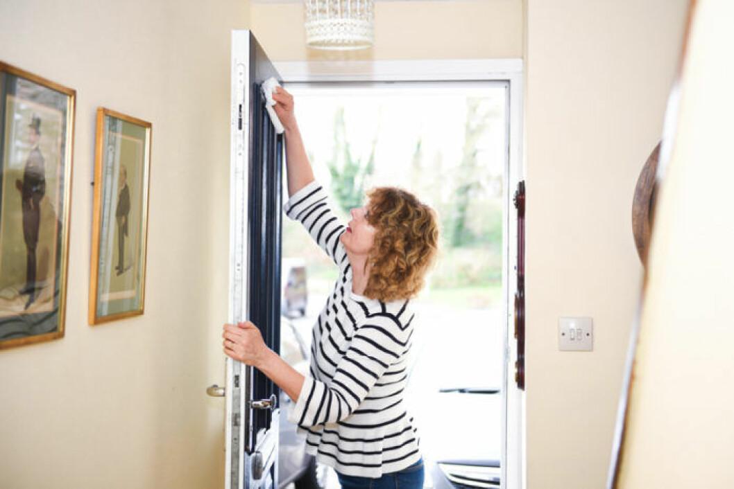 Kvinna torkar av dörr.