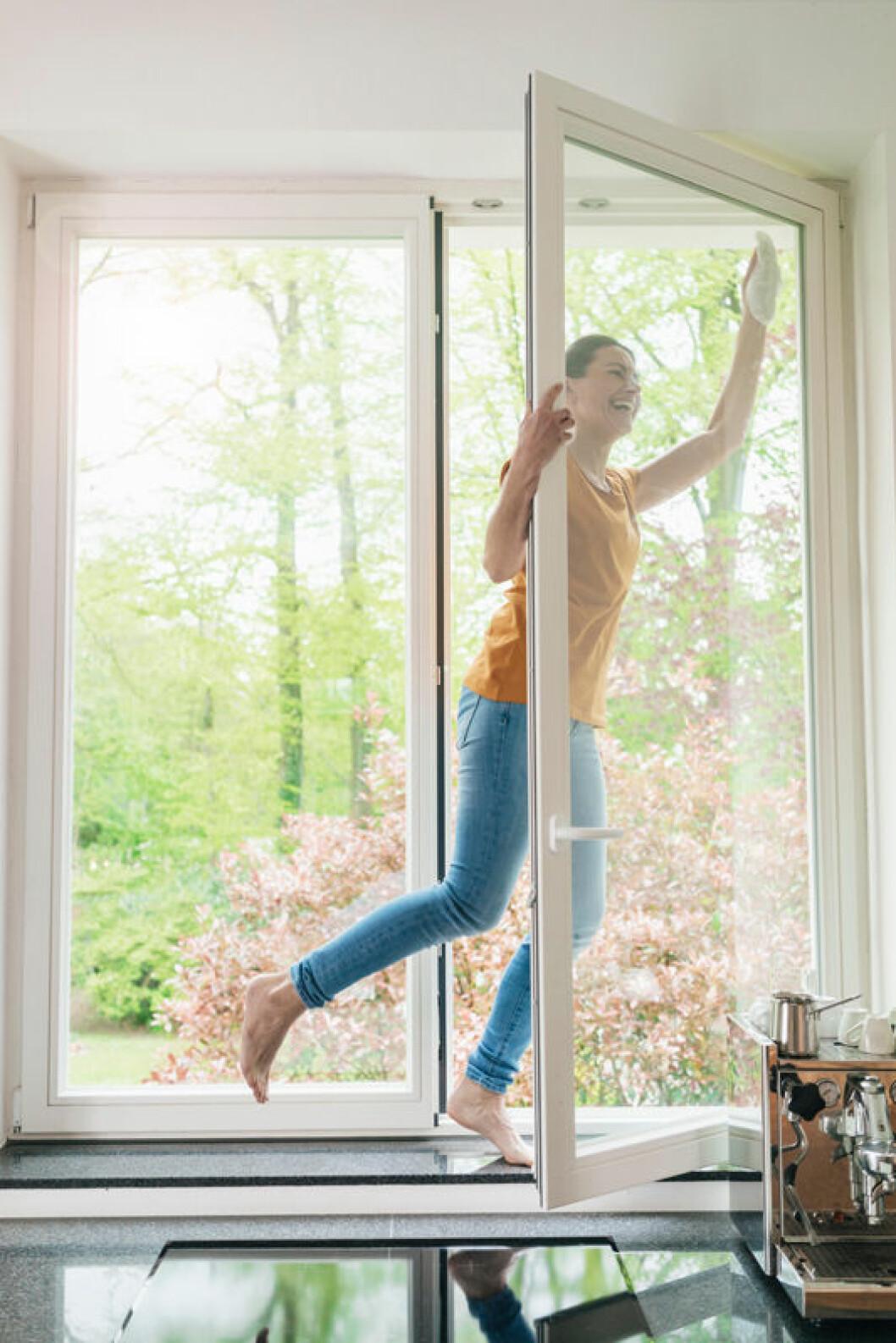 Kvinna putsar glasdörr.