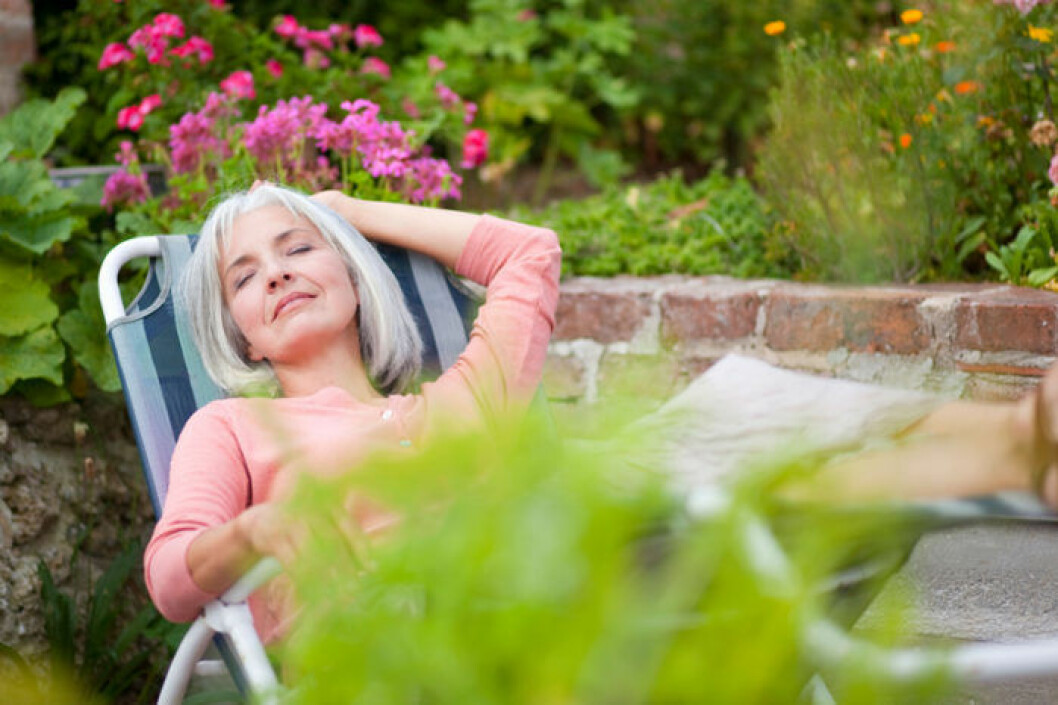Kvinna sover i solstol i trädgård.