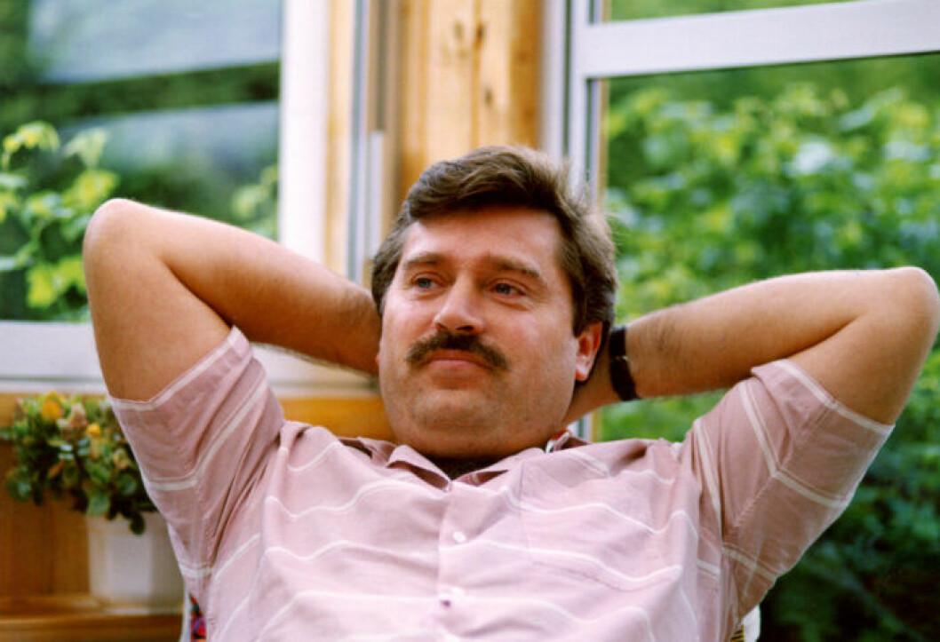 En man med mustasch i rosa skjorta håller händerna bakom huvudet