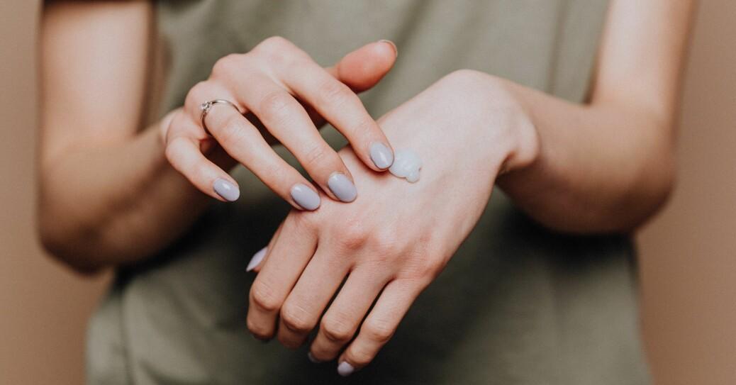 kvinna som smörjer sina händer