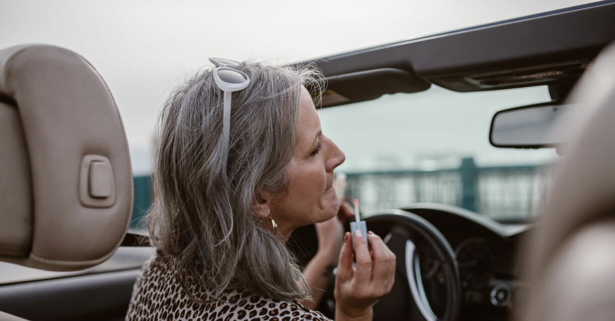 kvinna som målar läpparna i bilen