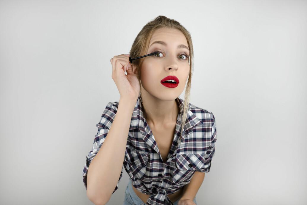 kvinna som borstar på mascara
