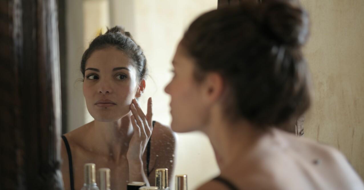 kvinna som kollar huden i spegeln