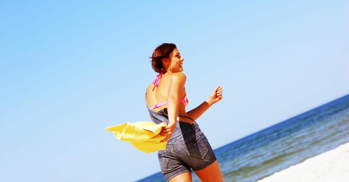 kvinna som njuter av sommaren på stranden