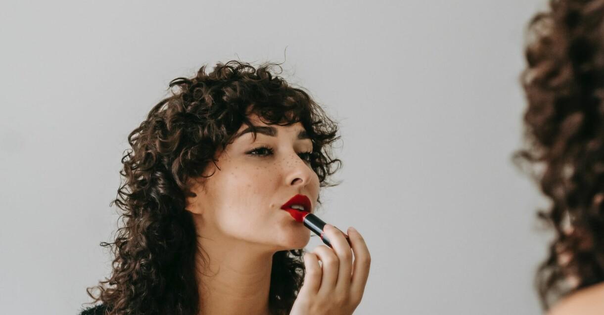 kvinna som målar läpparna vackert röda