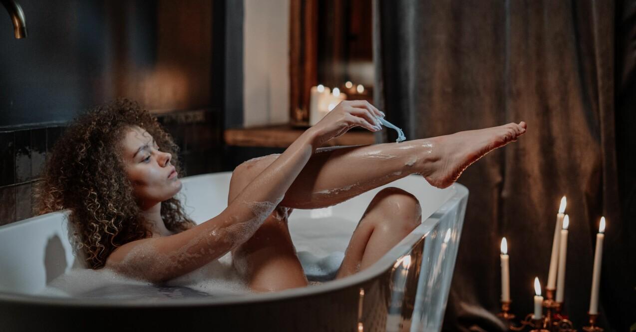 kvinna som rakar benen i badkaret