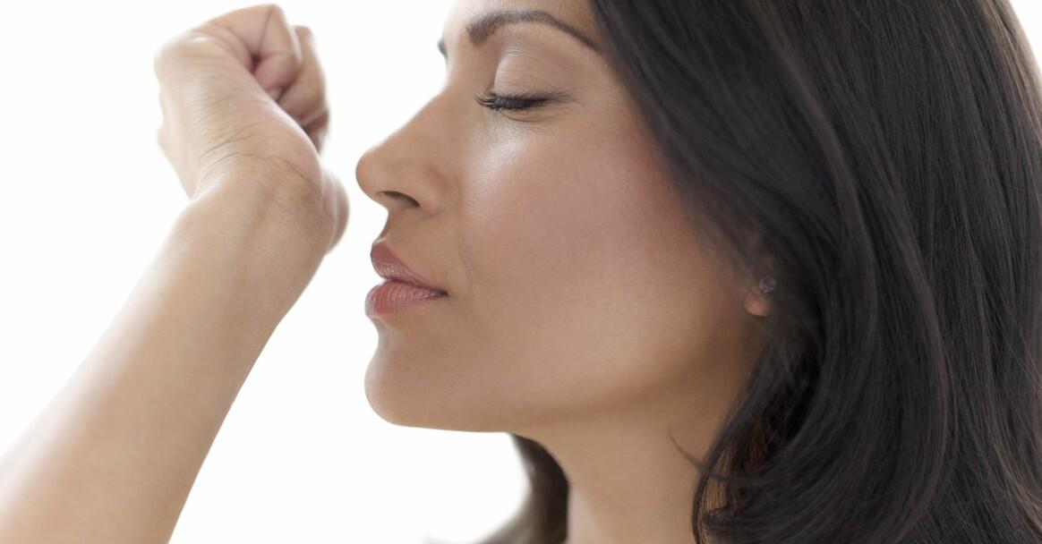 kvinna som doftar på parfym