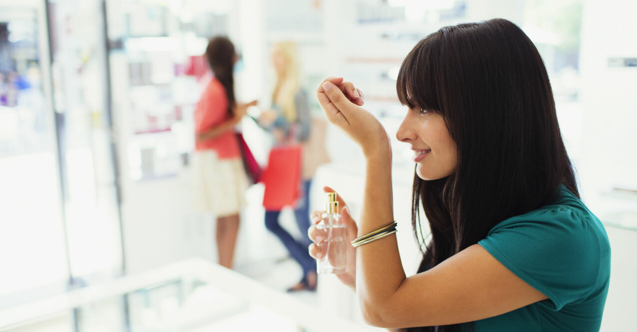 kvinna som testar parfym i affären