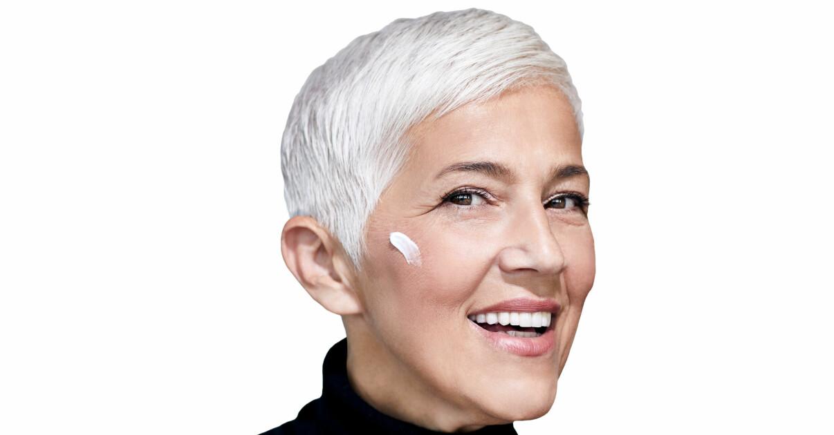 kvinna med vitt hår och creme på kinden