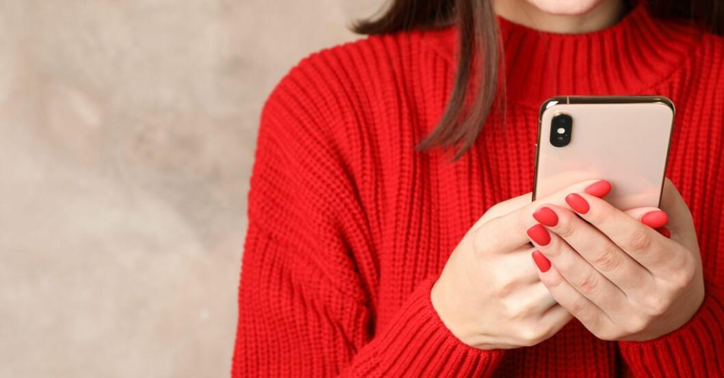 Kvinna i röd tröja som läser på en mobil.