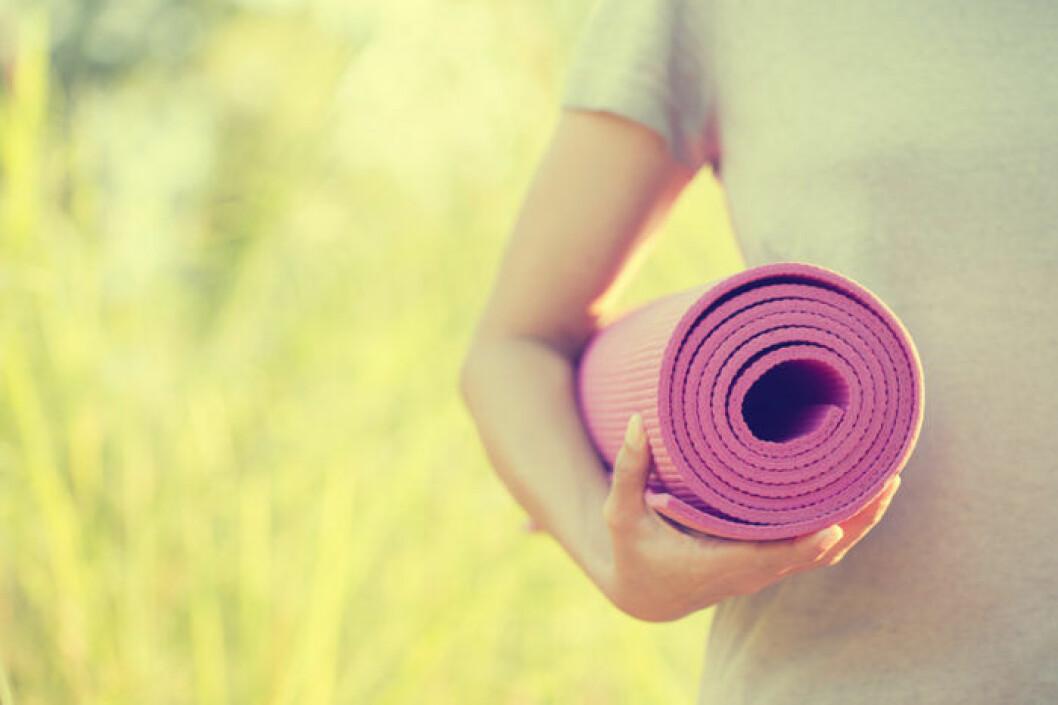 Kvinna med ihoprullad yogamatta.